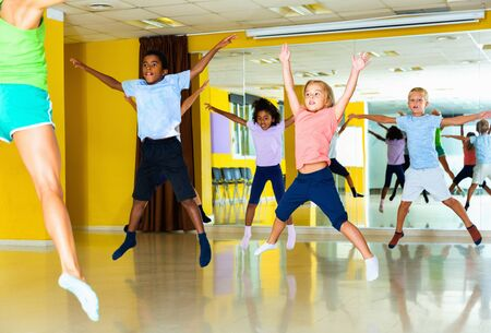 Group of  smiling positive   tweens jumping with female coach during exercising in choreography class