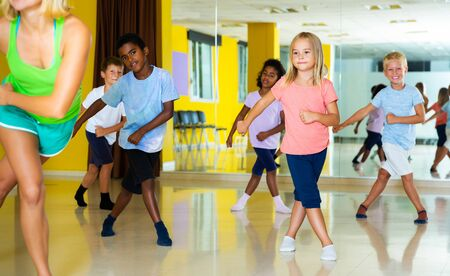 smiling little sportive children dancing synchronous group choreography with female coach in dance hall Banco de Imagens