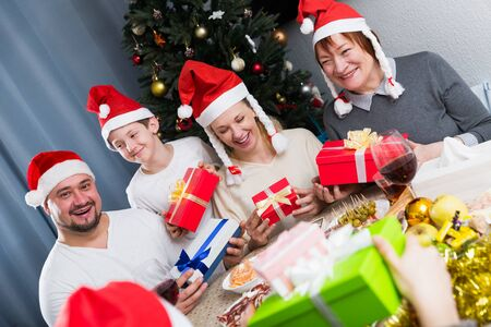 Three generations of happy family sitting around traditional holiday table with Christmas gifts Stockfoto