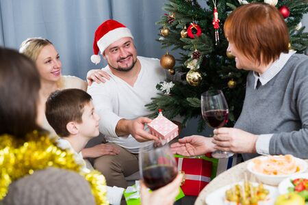 Smiling man giving presents to his family during Christmas celebration at home