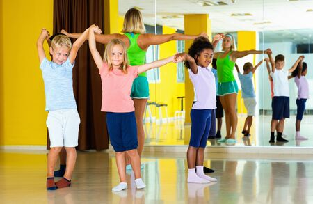 Group of glad cheerful tweens exercising folk dance, forming circle with female coach in choreography class