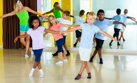 Preteen little boys and girls dancing rock-and-roll in pairs in choreography class with female trainer