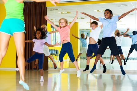 Group of happy sportive children with female teacher training in modern dance hall, jumping together