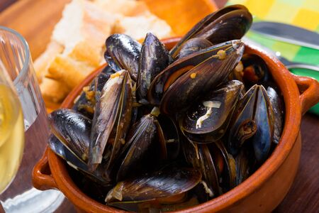 Delicious baked mussels on a bowl with onion sauce at table