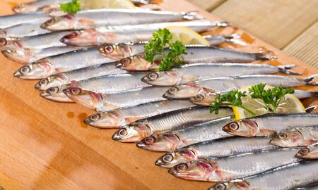 Fresh raw anchovies served on wooden surface
