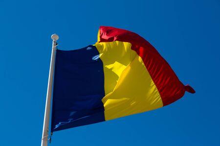 Romanian flag is fluttering in the wind outdoor. Banco de Imagens