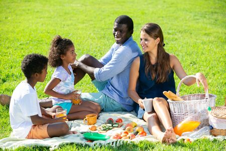 Portrait of cheerful interracial family with two children enjoying picnic on green meadow 版權商用圖片