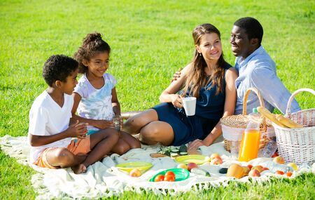 Happy mixed race couple with preteen children gaily spending time at picnic on green lawn