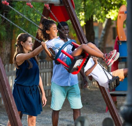 Cheerful mixed race parents riding children on swings, enjoying time during family walk