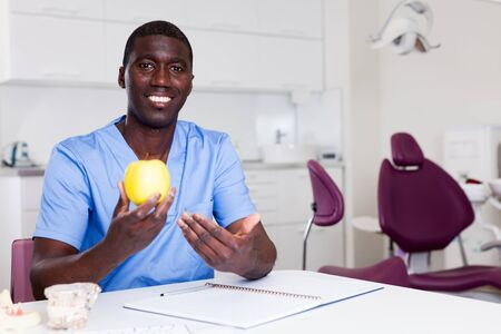Dentist afro american holds ripe apple in hand