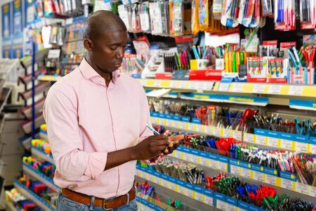 Portrait of cheerful  smiling Afro American man choosing ball pen at stationery store
