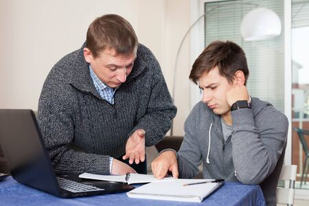 Father checks school assignments teenager son