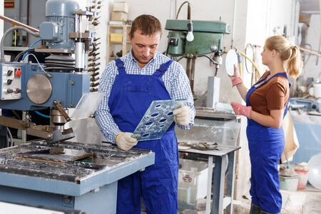 Confident male glazier working with glass on stationary drilling machine in workroom Stock fotó