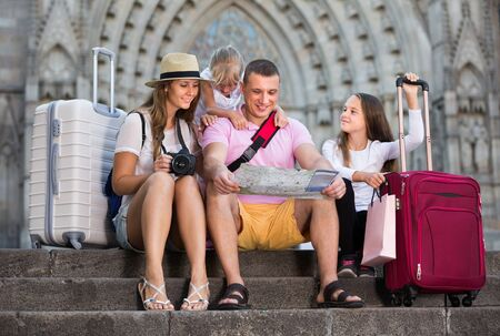 Portrait of  parents wth kids sitting on stone stairs near cathedral, using map