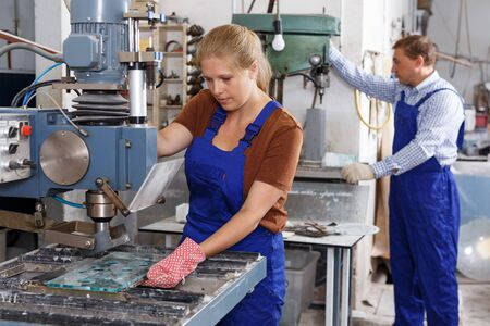 Smiling young woman working on glass drilling machine in workshop
