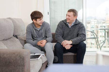 Father with his son are resting together and talking about teenage secrets