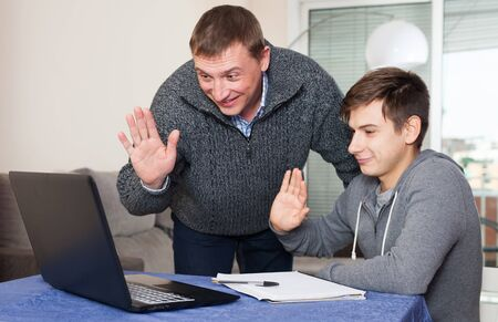 Smiling father with teenager son chatting with relatives online