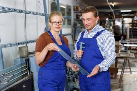 Portrait of man and woman in blue overalls working in glass workshop