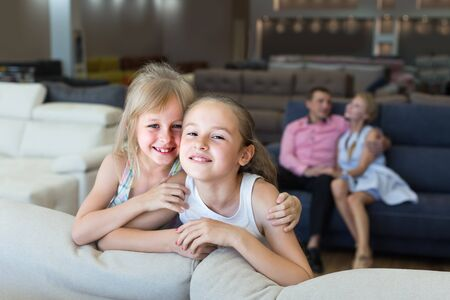 Kids are pleased of new sofa in furniture store. 版權商用圖片 - 128704821