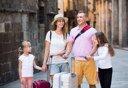 positive swedish  parents with two kids traveling together searching location on paper map 版權商用圖片