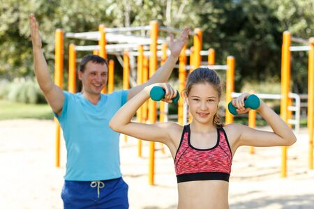 Sporty preteen girl exercising with dumbbells while father controlling process of training