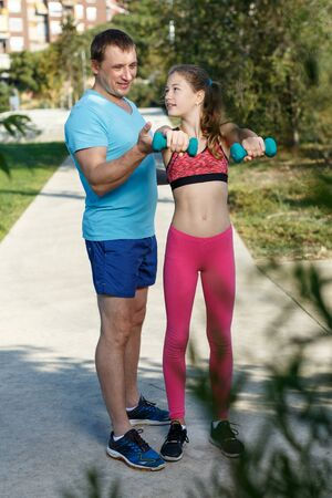 Smiling athletic man helping tweenager girl during workout with dumbbells in sunny day outdoors