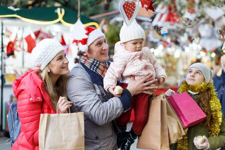 Portrait of cheerful man and woman and their happy daughters posing with paper bags near counters at Christmas fair