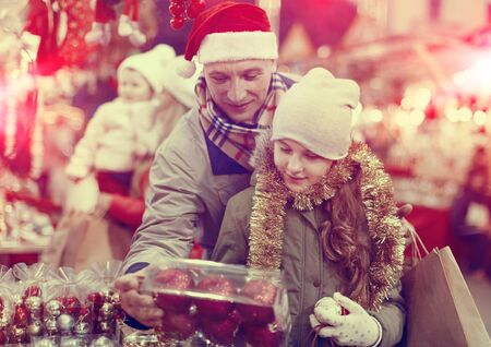 Happy father with his beautiful daughter choosing Christmas decoration at Christmas fair Reklamní fotografie