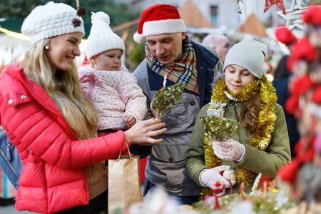 Portrait of cheerful man and woman with their happy daughters near counter buying Christmas decorations