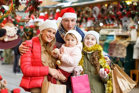 Happy family with two beautiful children female children holding paper bags with purchases at Christmas market