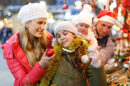 Portrait of happy young woman and her teenage daughter choosing Christmas toys at fair Reklamní fotografie