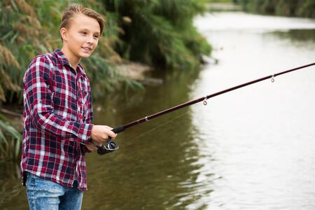Portrait of glad teenager boy casting line for fishing on lake