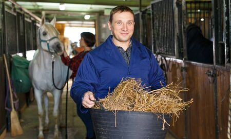 Man in working clothes feeding horse with hay at stable Stock Photo