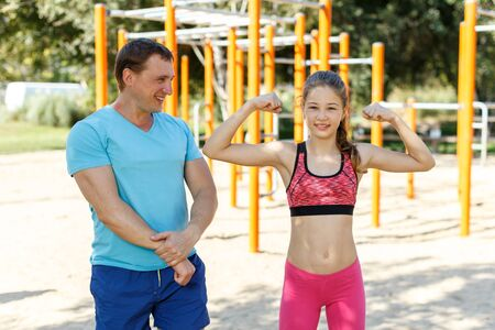 Smiling sporty man and tweenager girl posing together while exercising in summer park Banque d'images