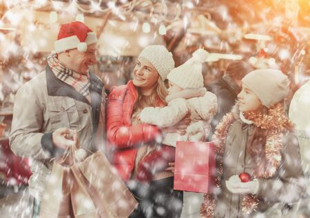 Family portrait of smiling parents with their two nice daughters at Christmas fair