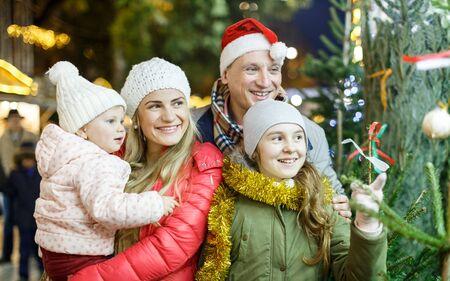 Happy family with two beautiful children female children choosing Christmas tree Reklamní fotografie