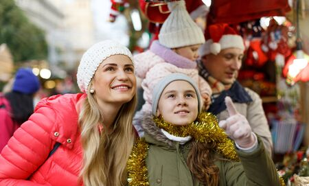 Smiling parents with their two nice daughters choosing Christmas toys at Christmas fair