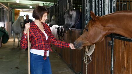 Portrait of cheerful woman horse farm worker standing at stable Stock Photo