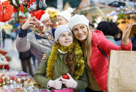 Smiling woman and her nice teenage daughter spending time at Christmas market Reklamní fotografie