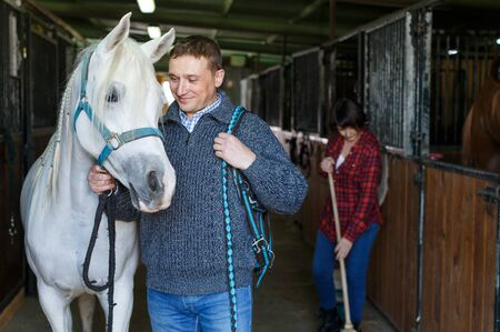 Portrait of positive man in casual clothes who works at horse stable