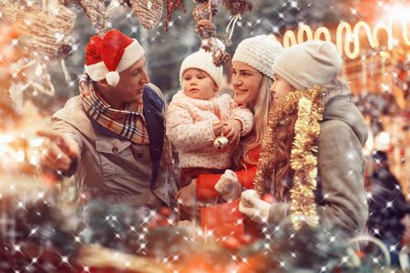 Happy family with two beautiful children female children spending time at Christmas fair