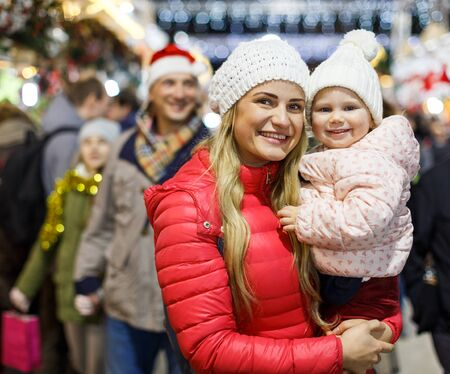 Portrait of happy young woman and her little daughter spending time at Christmas fair