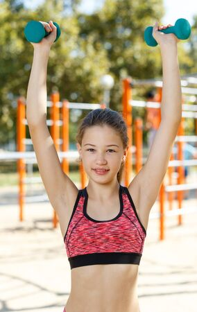 Sporty preteen girl exercising with dumbbells on outdoor sports ground in summer day