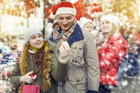Smiling man and his nice teenage daughter spending time at Christmas market