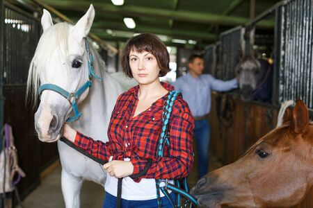 Portrait of woman farm worker standing at horse stable Stock Photo