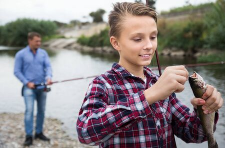 Positive young boy holding on hook freshwater fish on forest