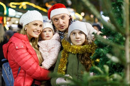 Cheerful parents with two daughters choosing Christmas tree at Christmas fair