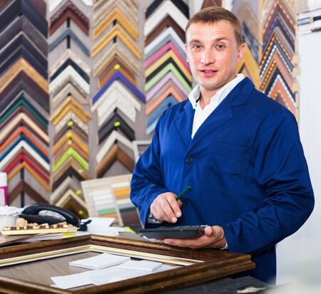 Cheerful  positive diligent man worker holding picture frame details on counter in studio Standard-Bild