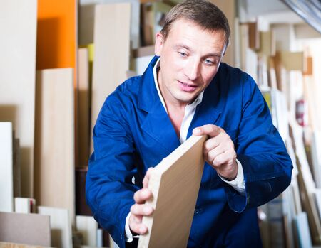 attentive male worker standing with plywood pieces in picture framing workshop