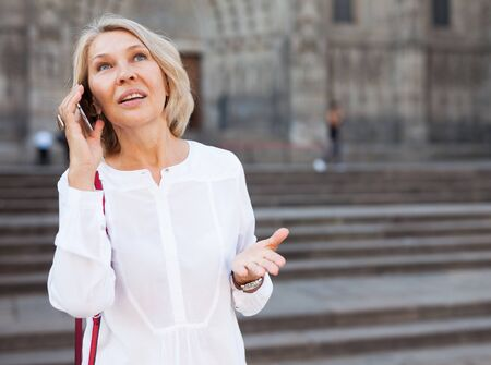Adult female is talking by phone with friend on the street outdoor Reklamní fotografie - 128829955
